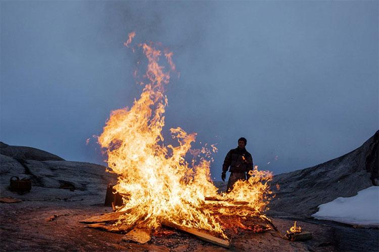 Sinh viên Febin Magar nhìn đống lửa thiêu đốt số gỗ còn sót lại trong một trại nghiên cứu.