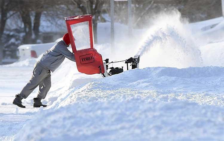 Aaron Braun phải gồng mình dùng máy đào đống tuyết dày chặn kín garage nhà mình
