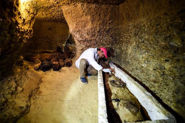 Một nhà khảo cổ đang xem xét xác ướp được đặt trong quan tài bằng đá.