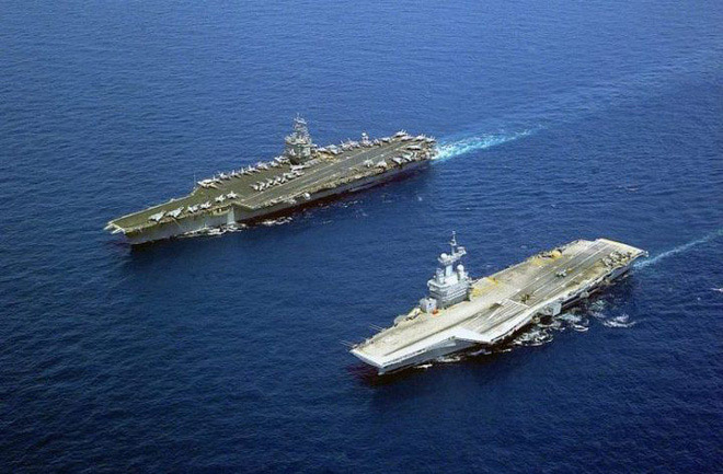 USS Enterpirse (trái) là tàu sân bay chạy bằng năng lượng hạt nhân đầu tiên và Charles de Gaulle (phải) đang di chuyển trên biển Địa Trung Hải vào ngày 16/5/2001