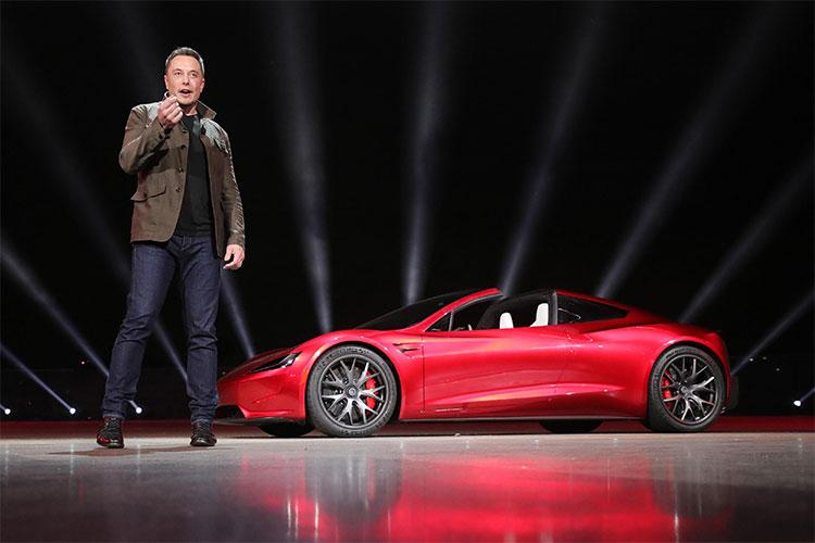 Tỷ phú Elon Musk, CEO SpaceX, đứng bên cạnh chiếc xe điện Tesla Roadster mui trần màu đỏ.