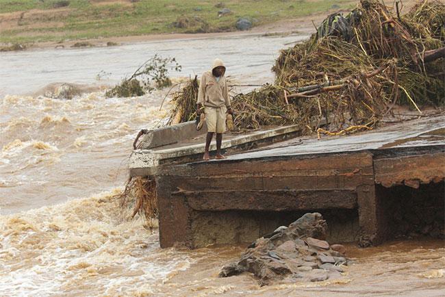 Một người đàn ông đứng bên rìa cây cầu bị sập ở Chimanimani, cách Harare, Zimbabwe