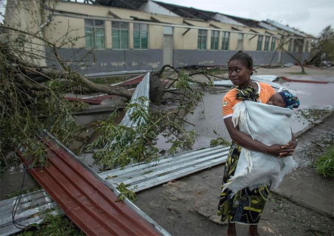 Một người phụ nữ bế con đến tòa nhà trường học đang được sử dụng làm nơi trú ẩn khẩn cấp