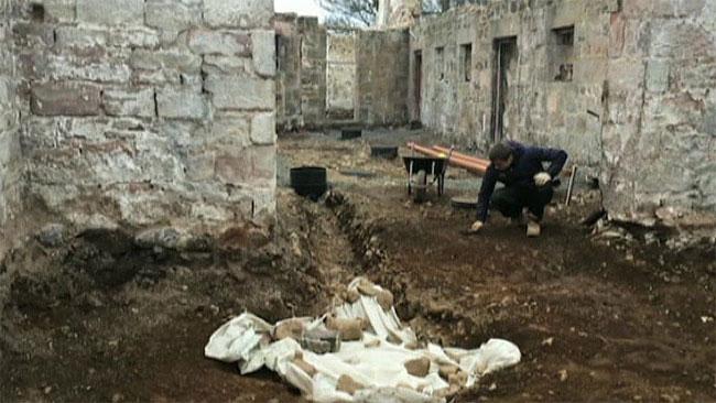 Một nhà khảo cổ đang tìm kiếm các hiện vật khác ở khu vực xung quanh hố chôn
