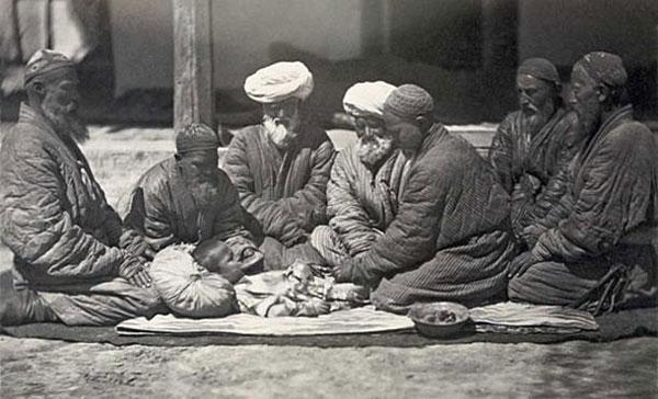 Cảnh một nhóm người đàn ông ngồi trên mặt đất gần một cậu bé đang được cắt bao quy đầu.