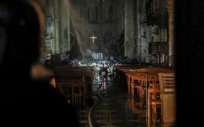 Lính cứu hỏa đưa vòi nước chữa cháy vào trong nhà thờ để dập tắt đám cháy còn âm ỉ