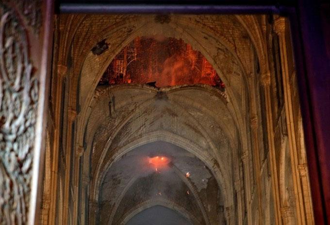 Trong ảnh, lửa vẫn cháy âm ỉ phía trên mái vòm cao hàng chục mét của nhà thờ.