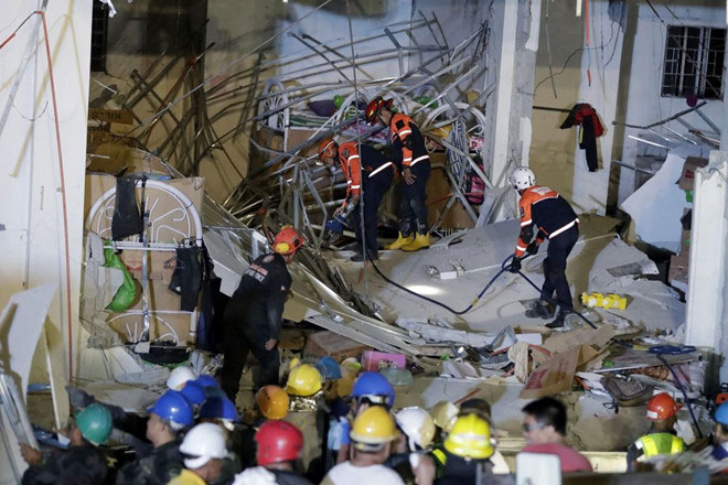 Lực lượng cứu hộ tìm kiếm nạn nhân vụ động đất trong đống đổ nát ở tỉnh Pampanga, Philippines.