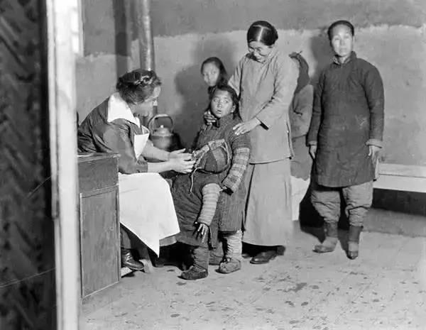 Một bác sỹ phương Tây đang khám bệnh cho em bé Trung Quốc tại Thiên Tân.