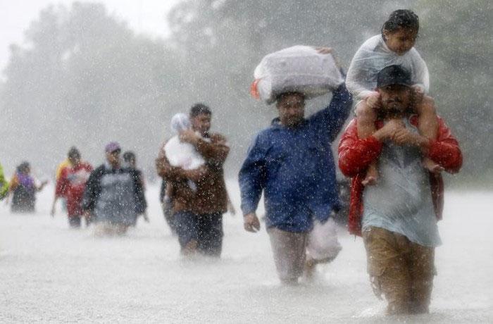 Dòng người lội bộ qua dòng nước lũ do siêu bão Harvey gây ra