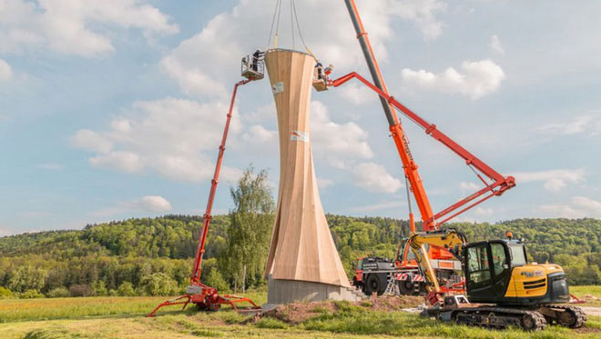 Một nhóm gồm 4 thợ tiến hành lắp ráp các tấm gỗ dán thành hình tòa tháp cao 14 mét.
