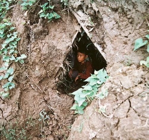 Em bé ngồi trong hầm tránh bom.