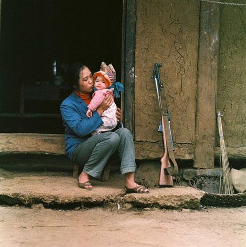 Nữ dân quân nựng yêu con nhỏ.