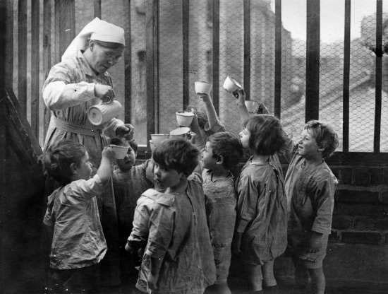 Một nữ y tá rót sữa cho những đứa trẻ tại một nhà trẻ ở Whitechapel, Anh