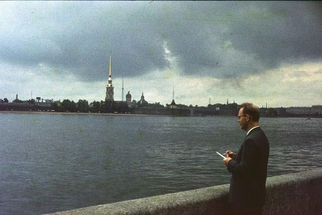 Một người đàn ông đứng bên bờ sông Neva nhìn về phía Pháo đài Peter and Paul.