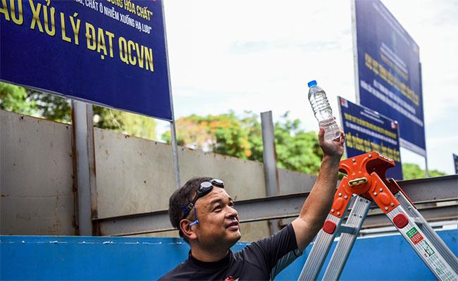 Ông Jun lấy mẫu nước tại bể này để so sánh với mẫu nước đóng chai đang được bán trên thị trường.
