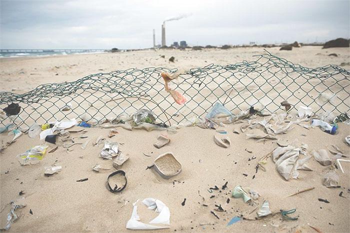 Sản phẩm nhựa bỏ đi nằm rải rác trên bãi cát ở bờ biển Địa Trung Hải thuộc lãnh thổ Ashkelon