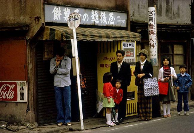 Người dân Tokyo đứng chờ tại một trạm xe buýt ở thành phố.