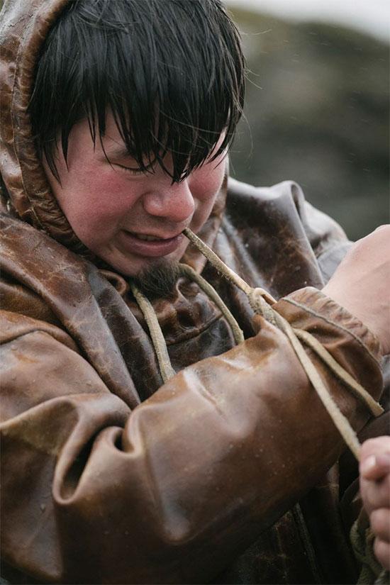 Một thanh niên thắt ống tay áo tuiliq bằng da hải cẩu của mình.