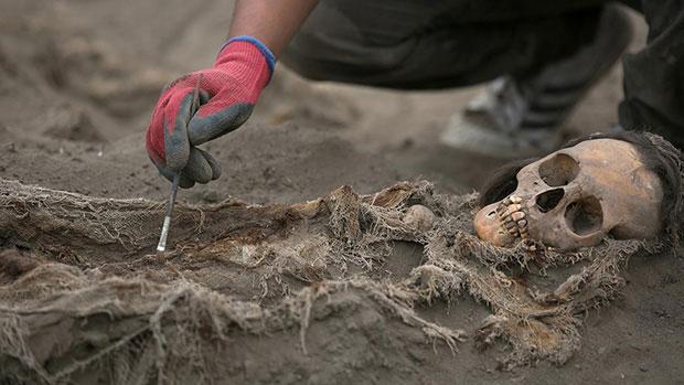 Các nhà khảo cổ đang kiểm tra một hài cốt được tìm thấy trong ngôi mộ tập thể.