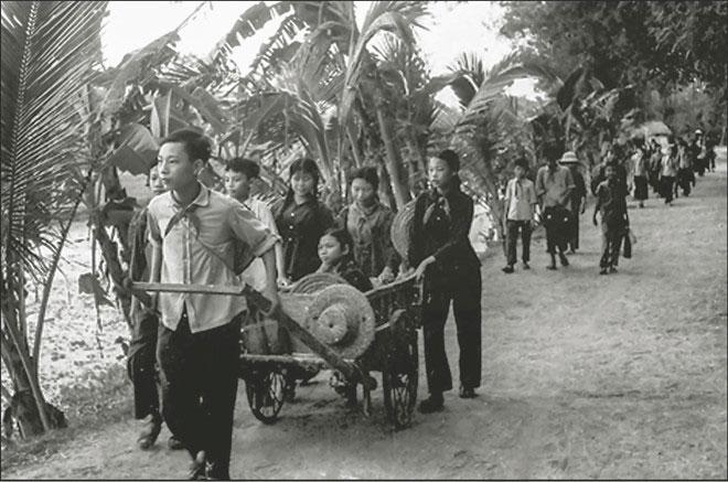 Các em học sinh trường THCS Quốc Oai giúp bạn khuyết tật đến trường, năm 1971.