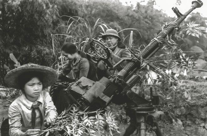 Một học sinh bên bố mẹ trên chiến hào đánh Mỹ tại xã Vinh Quang, huyện Tiên Lãng, Hải Phòng, năm 1971.