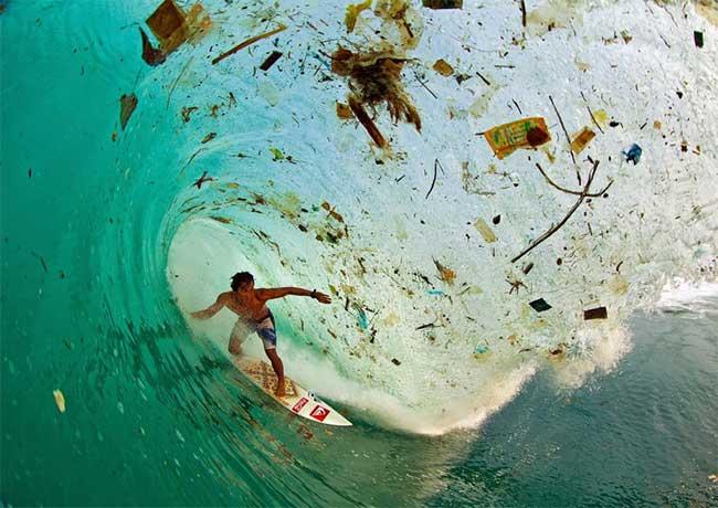 Một người đang lướt sóng giữa những con sóng đầy rác ở một vịnh trên đảo Java, Indonesia