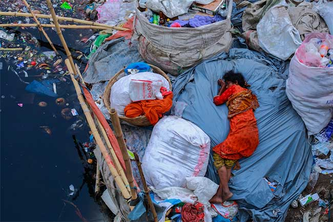 Một phụ nữ ngủ trên bờ sông ngập đầy rác ở Dhaka Bangladesh.