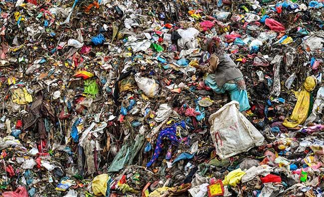 Một người đang tìm kiếm những thứ có thể bán được trong đống rác khổng lồ