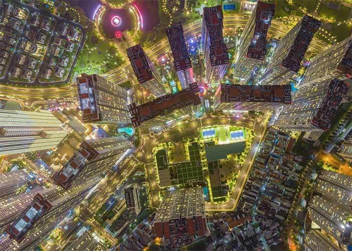 Những tòa cao ốc và ánh đèn từ các con đường khi nhìn trên cao trông như một bảng vi mạch điện tử.