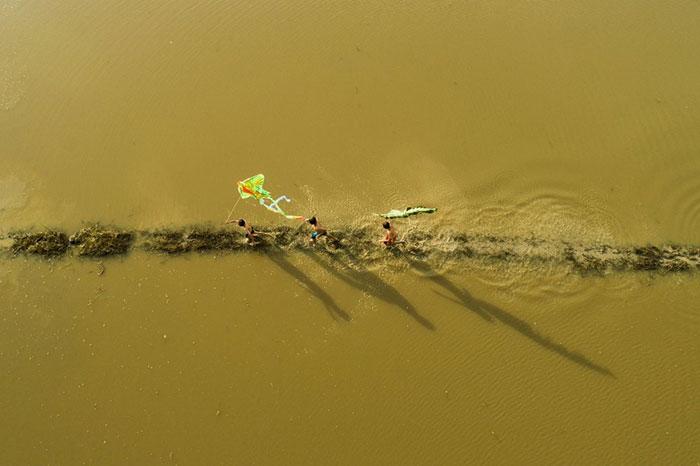 Trẻ em thả diều trên một con đê đang bị xây xung quanh bởi nước lũ ở Đồng bằng sông Cửu Long.