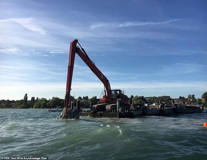 Máy xúc được đưa bằng thuyền ra giữa đáy hồ để giúp loại bỏ trầm tích chôn vùi cấu trúc bí ẩn