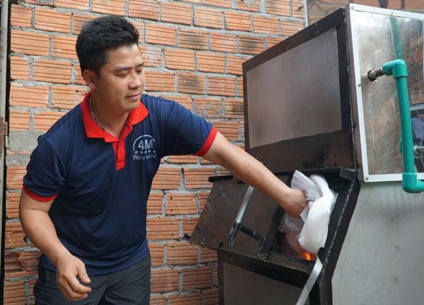 Kỹ sư Nguyễn Nở cho rác vô cơ qua cửa lò đốt.