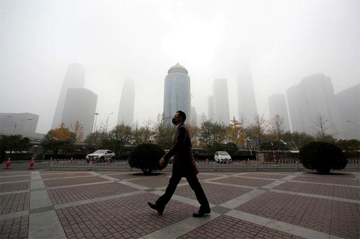 Một người đàn ông bịt khẩu trang kín mặt và bước đi qua một quảng trường tại Bắc Kinh, Trung Quốc.