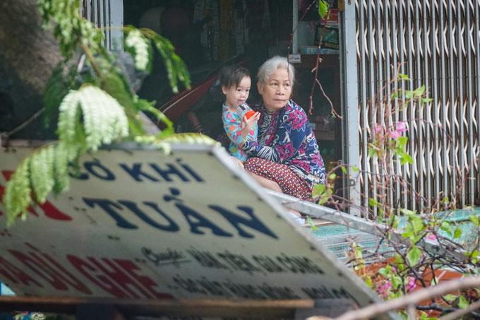 Hai bà cháu ôm nhau nhìn cây cối, bảng hiệu đổ sập trước nhà tại phường Hải Cảng.