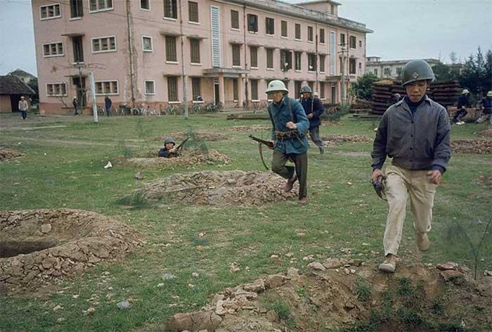 Dân quân Hà Nội luyện tập trên thao trường, phía trước một nhà máy sản xuất xe đạp.