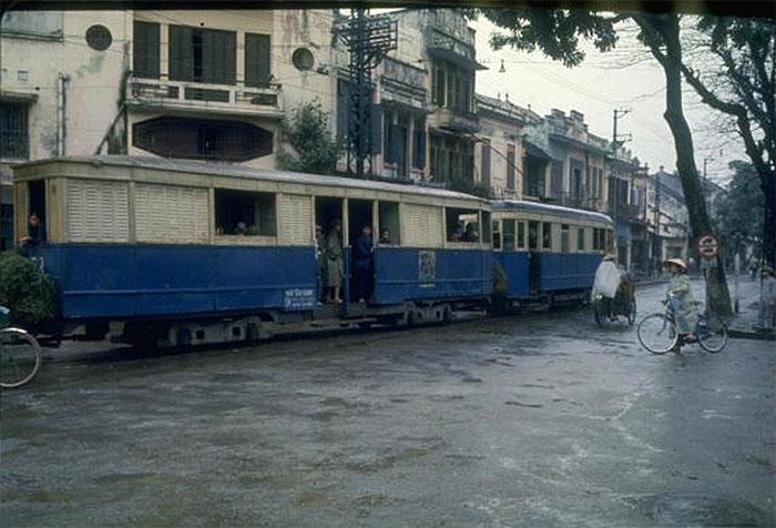 Những toa xe điện cũ kỹ chậm chạp chạy qua trung tâm Hà Nội.