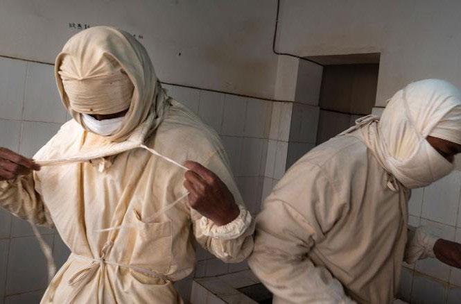 Nhân viên một trung tâm phòng chống dịch bệnh Trung Quốc mặc đồ bảo hộ trước khi bước vào phòng thí nghiệm