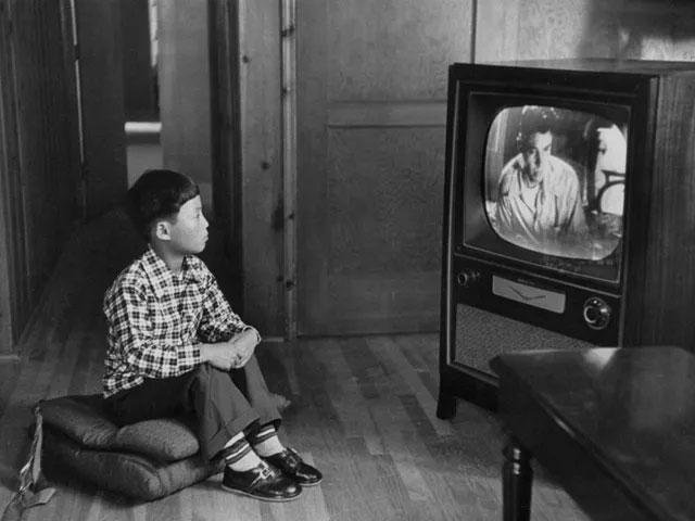 Cậu bé gốc Hàn Kang Koo Ri đang ngồi xem TV trong gia đình bố mẹ nuôi ở Los Angeles.