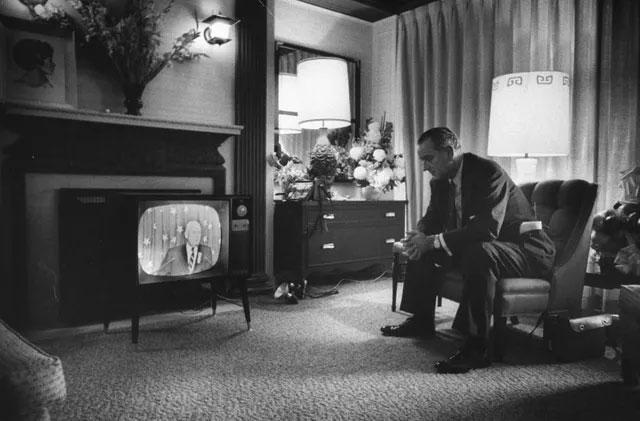 Người đàn ông theo dõi tin tức từ phòng khách sạn.