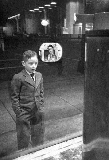 Một cậu bé tranh thủ đứng xem chương trình truyền hình từ một chiếc TV đặt trong cửa hiệu.