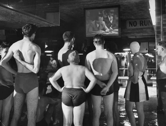 Những người đi bơi tại một bể bơi công cộng chăm chú theo dõi một bản tin thời sự.
