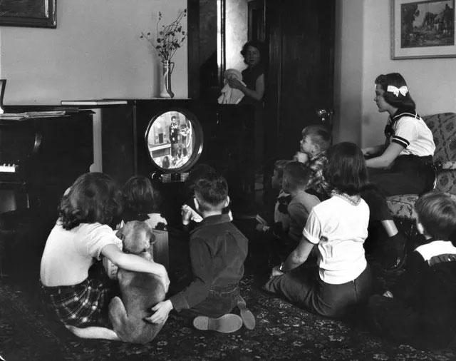 Những đứa trẻ ngồi xem TV chăm chú.