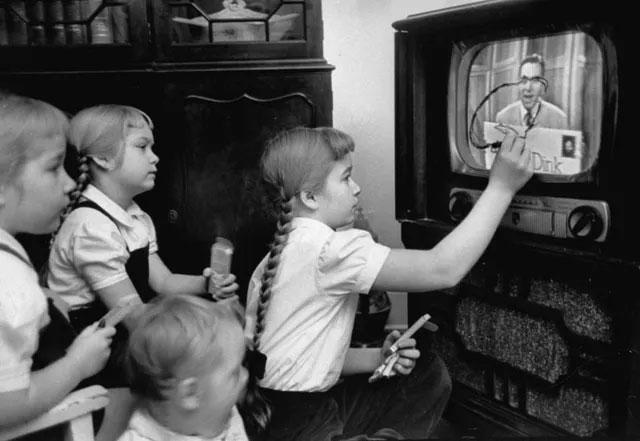 Một cô bé đang tập trung vẽ lên màn hình TV