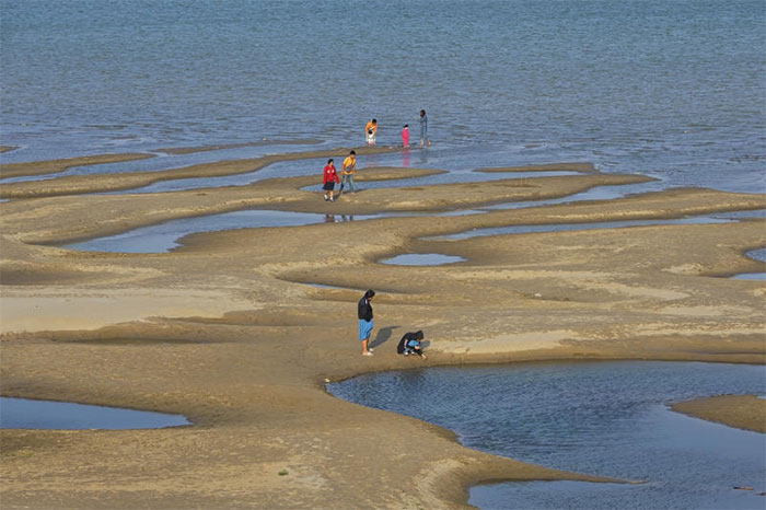 Các du khách đứng trên bãi cát ở sông Mê Kông thuộc tỉnh Nakhon Phanom, đông bắc Thái Lan hôm thứ Tư, 4/12.