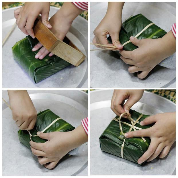 Sau khi gói xong, dùng một tay giữ phần lá để cố định đồng thời nhẹ nhàng khuôn bánh ra.
