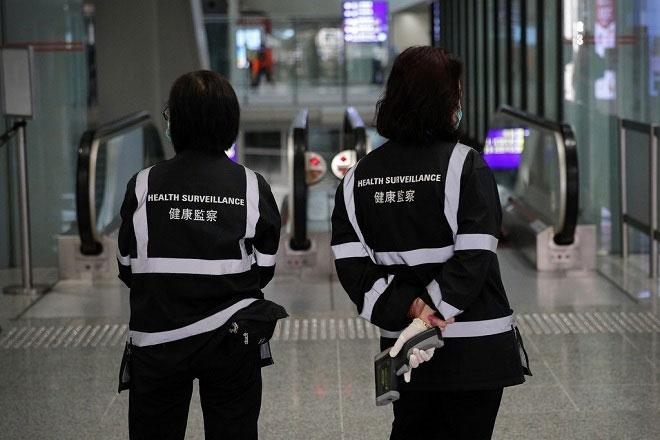 Đội giám sát y tế bằng máy đo nhiệt độ cơ thể ở sân bay Hong Kong.