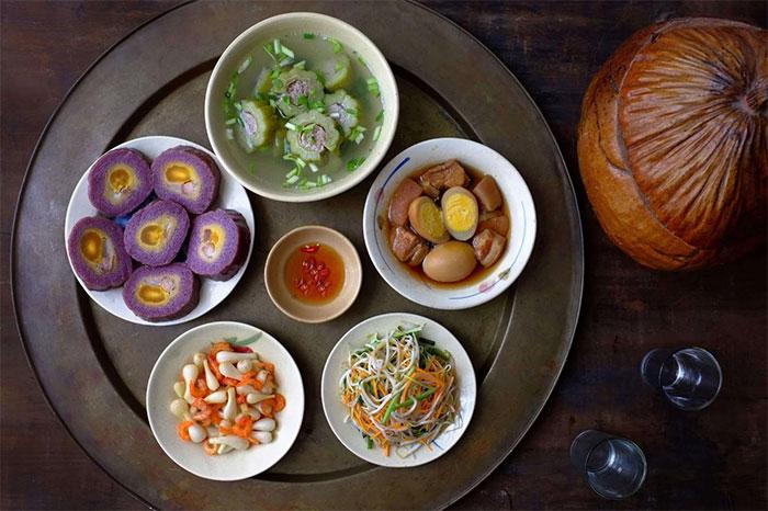Mâm cơm Tết miền Nam có bánh Tét nhân chuối đậu, canh khổ qua, thịt kho hột vịt...