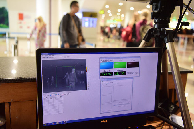 Tất cả hành khách nhập cảnh phải đi qua máy đo thân nhiệt từ xa, ảnh chụp tại sân bay Nội Bài ngày 21/1.