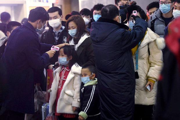 Người lớn và trẻ em được kiểm tra thân nhiệt tại nhà ga và sân bay ở Vũ Hán.